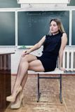 Strict young blonde teacher reflects on who to check homework. Strict young blonde teacher sits on a chair in the classroom against a blackboard and reflects on Stock Photo