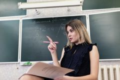 Strict young blonde teacher reflects on who to check homework. Strict young blonde teacher sits on a chair in the classroom against a blackboard and reflects on Stock Photography