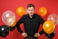 Strict young man in black classic shirt standing with arms akimbo on bright red background air balloons. St. Valentine`s. International Women`s Day Happy New stock image