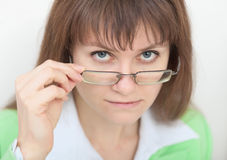 Strict young woman looks at us over eyeglasses Royalty Free Stock Image