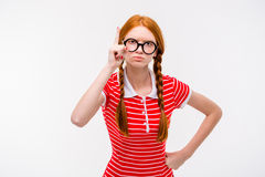 Strict young woman with two braids pointing up Royalty Free Stock Image