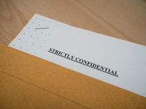 Strictly Confidential document in brown vintage envelope on wood table, in macro Royalty Free Stock Photos