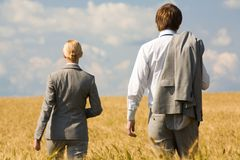 Stride. Rear view of associates in suits walking in wheat field Royalty Free Stock Images