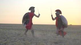 Striden av två romerska soldater i röda kappor i mitt av fältet för gryning arkivfilmer
