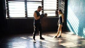 Stridinstruktörutbildning passade den vita kvinnliga boxaren på idrottshallen i ultrarapid lager videofilmer