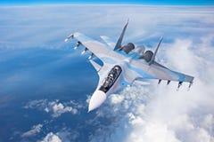 Stridjaktflygplan på en militär beskickning med vapen - raket, bombarderar, vapen på vingar flyger högt i himlen ovanför molnen royaltyfri foto