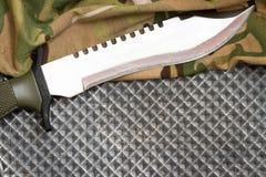 Stridkniv på militärt kamouflagetyg och metallbakgrund Royaltyfri Foto
