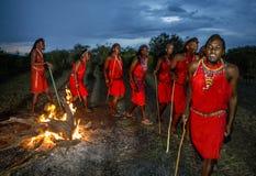 Strijders de Masai-stam het dansen rituele dans rond de brand laat in de avond Stock Afbeelding