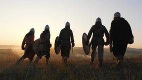 Strijders Vikingen die en op gebied gaan stoping en bekijken mooie zonsondergang stock video