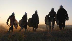 Strijders Vikingen die en op gebied gaan stoping en bekijken mooie zonsondergang stock videobeelden