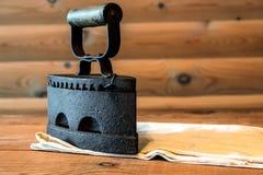 Strijkijzer oud ijzer die op een houten lijst met een doek, de Russische ijzer 19de eeuw liggen Royalty-vrije Stock Afbeeldingen