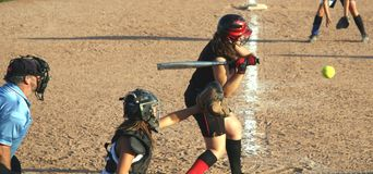 Strike. A young lady, or teen, batting in a fastball game Royalty Free Stock Images