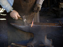 Strike while the iron is hot. Metalsmith fabricating and shaping steel stock photography
