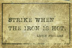 Strike iron LP. Strike when the iron is hot - ancient Latin proverb printed on grunge vintage cardboard Royalty Free Stock Images