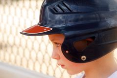 Strike Out-Dejection. A little league player in the dug-out who is about to cry after striking out in his game.  (He swung hard, though Royalty Free Stock Photography