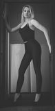 Strike a pose. Blond woman in black tight pants and high heels standing in doorway stock photography