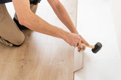 Strikes with a soft hammer on the part with a lock, for fixing. Installing laminate flooring fitting the next piece -. Male worker installing new wooden laminate royalty free stock photography