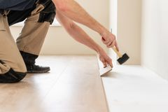 Strikes with a soft hammer on the part with a lock, for fixing. Installing laminate flooring fitting the next piece -. Male worker installing new wooden laminate stock images