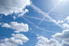Striking blue sky with fluffy white clouds, criss crossed with vapour trails and power lines royalty free stock images