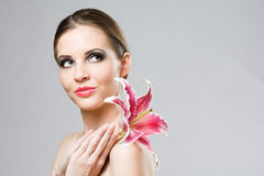 Striking brunette beauty with colorful lily. Stock Photos
