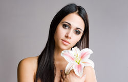 Striking brunette beauty with flower. Stock Photo