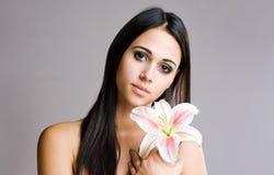 Striking brunette beauty with flower. Stock Photo