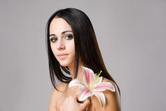 Striking brunette beauty with flower. Stock Photos