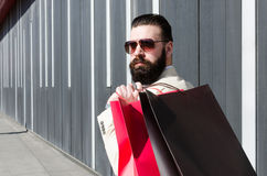 Striking man carries a shopping bag over her shoulder and lookin Royalty Free Stock Photography