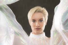 Striking portrait of young woman wrapped in gossamer cape. Royalty Free Stock Photography