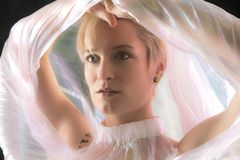 Striking portrait of young woman wrapped in gossamer cape. Royalty Free Stock Photos