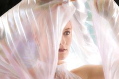 Striking portrait of young woman wrapped in gossamer cape. Royalty Free Stock Photo