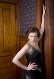 Striking A Pose. Beautiful young brunette woman dressed in an elegant evening gown posing for the camera Stock Image