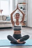 Striking the pose. Beautiful young Asian woman in sports clothing doing yoga while relaxing at home royalty free stock photo