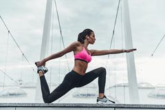 Striking the pose. Modern young woman in sports clothing stretching while warming up outdoors royalty free stock photo