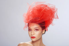 Striking Red Themed Woman With Creative Headpiece Royalty Free Stock Images