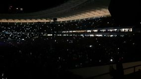 Thousands of people looking at a rock concert and lighting flashlights in slo-mo
