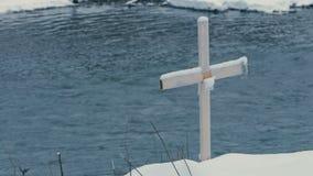 Wooden cross standing on a mountain riverbank in Bukovel in winter in slo-mo