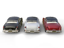 Striking vintage cars - black, white and cherry red. Top back view Royalty Free Stock Photo