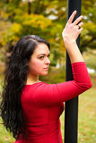 Striking woman in red posing on lamp post Stock Photos