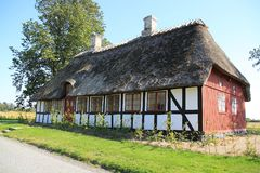 Striking wooden house at the countryside in Denmark in the summer. Camping with the wooden building with thatched roof is standing at the island Funen in royalty free stock images