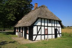 Striking wooden house at the countryside in Denmark in the summer. Camping with the wooden building with thatched roof is standing at the island Funen in stock photography