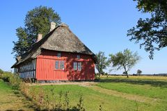 Striking wooden house at the countryside in Denmark in the summer. Camping with the wooden building with thatched roof is standing at the island Funen in stock image