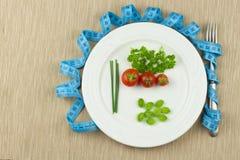 Strikt banta mot fetma Diet-grönsaken bantar Tomater på en plätera Rå grönsaker på en vit platta och ett mäta band arkivfoto