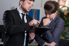 Strikt framstickande som talar med sekreteraren arkivfoton