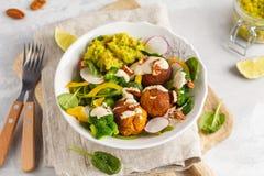 Strikt vegetarian bakade sötpotatisköttbullar, guacamole och grönsaksal Arkivbilder