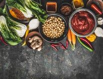 Strikt vegetarian- och vegetarianmatingredienser: kikärtar, örter, kryddor, ingefära och bok som är choy på lantlig bakgrund, bäs arkivbild
