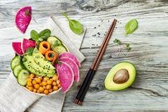 Strikt vegetarian, recept för detoxBuddhabunke med avokadot, morötter, spenat, kikärtar och rädisor Bästa sikt, lekmanna- lägenhe royaltyfri fotografi