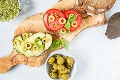 Strikt vegetarian skjuter in med avokadot, tomater och groddar Royaltyfri Foto