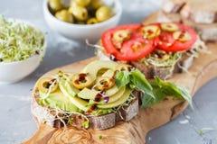 Strikt vegetarian skjuter in med avokadot, tomater och groddar Royaltyfri Bild