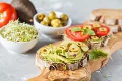 Strikt vegetarian skjuter in med avokadot, tomater och groddar Arkivbild